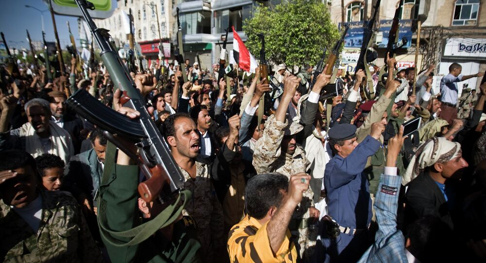 Shiite rebels known as Houthis hold up their weapons as they chant slogans during a protest to denounce the Saudi aggression in Sanaa, Yemen, Wednesday, April 22, 2015
