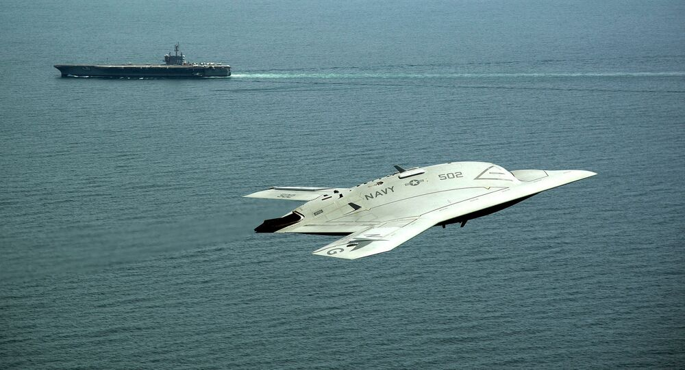 An X-47B Unmanned Combat Air System (UCAS) demonstrator flies near the aircraft carrier USS George H.W. Bush.