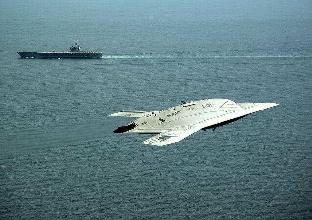 An X-47B Unmanned Combat Air System (UCAS) demonstrator flies near the aircraft carrier USS George H.W. Bush.