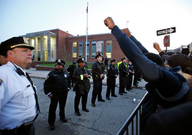 Marchers raise their fists in front of Baltimore police guarding the department's Western District police station during a march for Freddie Gray, Wednesday, April 22, 2015, in Baltimore