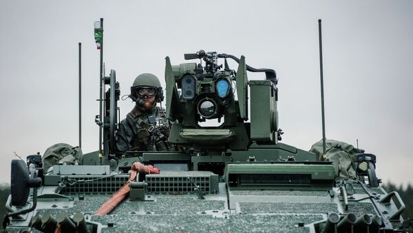 A soldier from the Swedish Armed Forces, looks on from top of the Patria XA-360 AMV (Armored Modular Vehicle) at Hagshult Airbase - Sputnik International