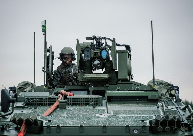 A soldier from the Swedish Armed Forces, looks on from top of the Patria XA-360 AMV (Armored Modular Vehicle) at Hagshult Airbase