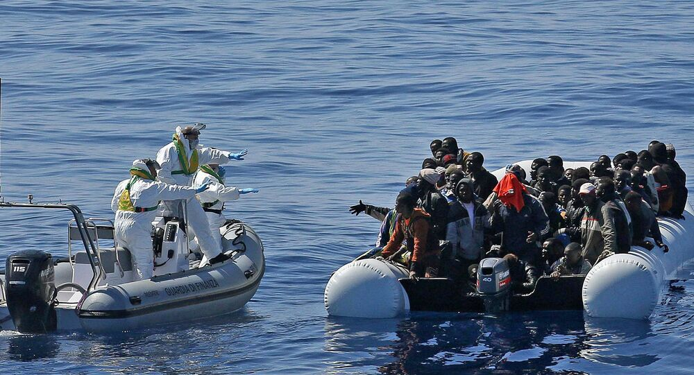Migrants crowd and inflatable dinghy as rescue vassel  Denaro  (not in picture) of the Italian Coast Guard approaches them, off the Libyan coast, in the Mediterranean Sea