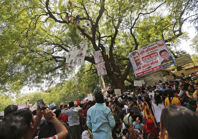 Supporters of Aam Aadmi (Common Man) Party (AAP) watch as others try to rescue a farmer who hung himself from a tree during a rally organized by AAP, in New Delhi April 22, 2015