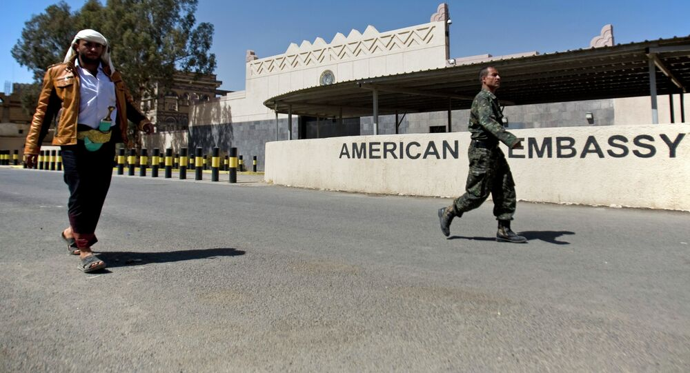 Houthi Yemenis walk past the gate of the main entrance of the closed US embassy after Yemeni police opened the road in front of it, in Sanaa, Yemen