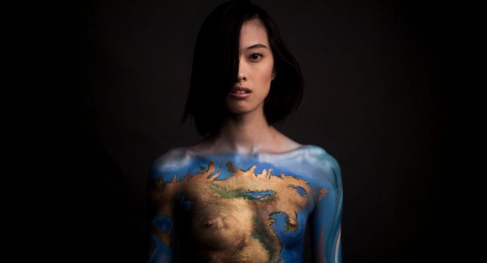US model Kelly Chin poses with a body painting to advertise a new pro-vegan Earth Day by PETA (People for the Ethical Treatment of Animals) Asia in Beijing on April 20, 2015.