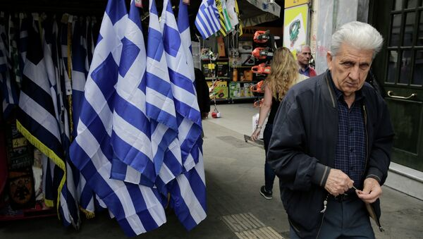 A man walk past a kiosk with Greek flags for sale in central Athens. - Sputnik International