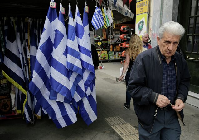 A man walk past a kiosk with Greek flags for sale in central Athens.
