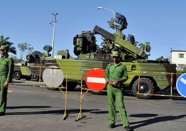 Cuban soldiers guard military vehicles, during a parade rehearsal at Revolution Square in Havana