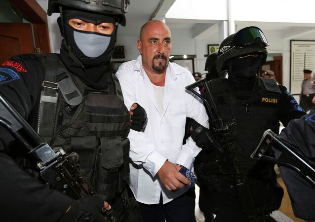Serge Atlaoui, center, a French national who is on death row after being convicted of drug offences, is escorted by armed police officers upon arrival for his judicial review hearing at the district court in Tangerang, Indonesia.