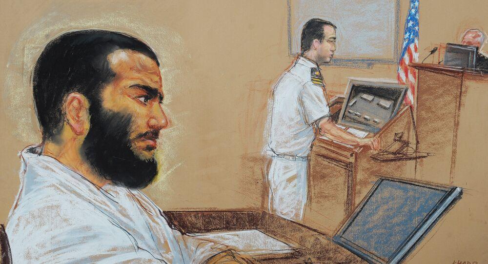 Canadian-born accused terrorist Omar Khadr doodling as his lead defense counsel, Navy Lieutenant Commander William Kuebler, addresses the judge