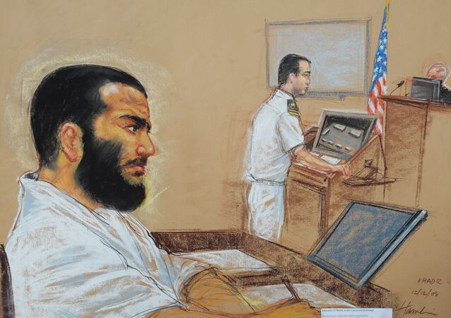 Canadian-born accused terrorist Omar Khadr doodling as his lead defense counsel, Navy Lieutenant Commander William Kuebler, addresses the judge