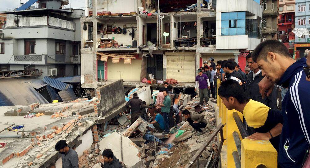 People survey a site damaged by an earthquake, in Kathmandu, Nepal