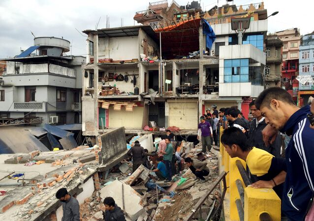 People survey a site damaged by an earthquake, in Kathmandu, Nepal
