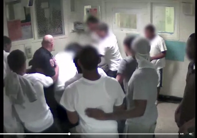 A screenshot of a Rikers CCTV video showing a corrections officer and inmates beating Kalief Browder