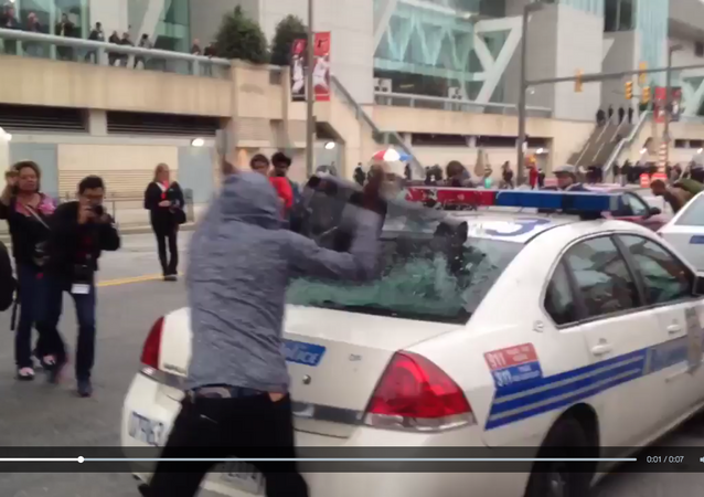 Screenshot from cell phone video that shows a protester smash a police car window during an anti-police brutality rally in Baltimore on April 25, 2015
