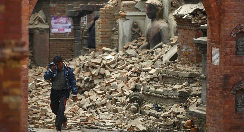 A man cries as he walks on the street while passing through a damaged statue of Lord Buddha a day after an earthquake in Bhaktapur, Nepal