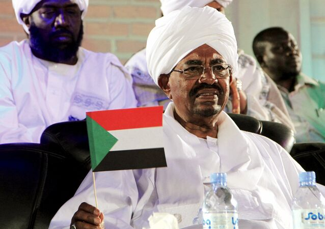 National Congress Party's (NCP) presidential candidate, Sudan's President Omar Hassan al-Bashir holds a Sudan national flag during a campaign rally, ahead of the 2015 elections, in Omdurman April 9, 2015.