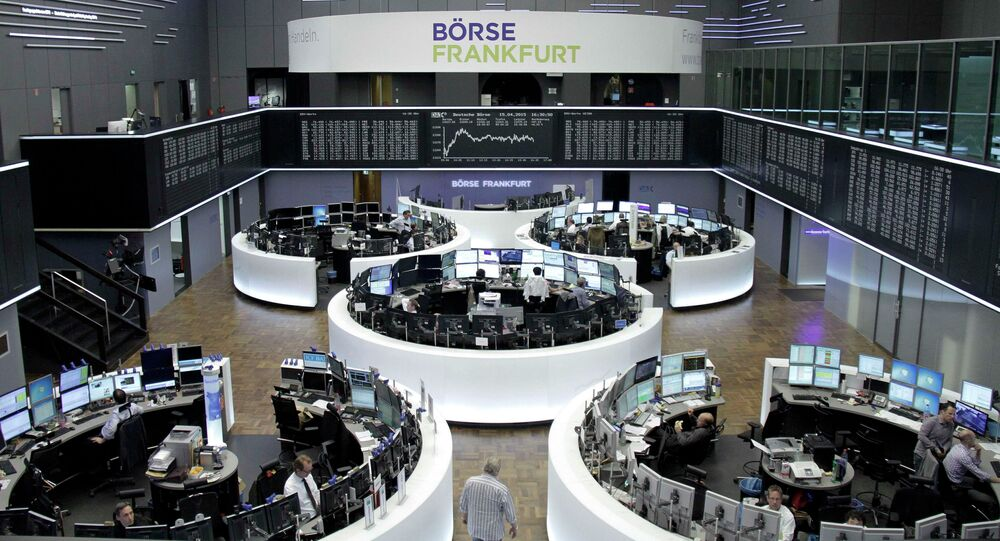 Traders are pictured at their desks in front of the DAX board at the Frankfurt stock exchange April 15, 2015