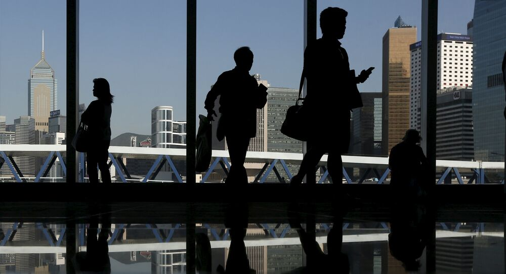 Mainland Chinese visitors admire the skyline of the financial Central district inside a shopping mall in Hong Kong April 14, 2015