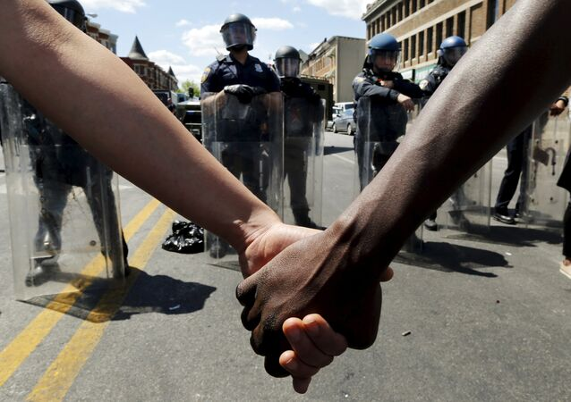 Members of the community hold hands in front of police officers in riot gear outside a recently looted and burned CVS store in Baltimore, Maryland, United States April 28, 2015