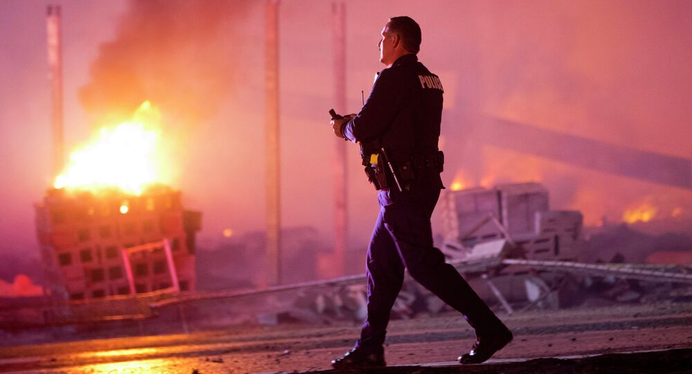 A police officer walks by a blaze, Monday, April 27, 2015, after rioters plunged part of Baltimore into chaos, torching a pharmacy, setting police cars ablaze and throwing bricks at officers