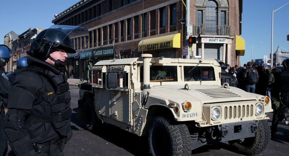 A National Guard vehicle drives by a Maryland State Trooper Tuesday, April 28, 2015, in the aftermath of rioting following Monday's funeral for Freddie Gray.
