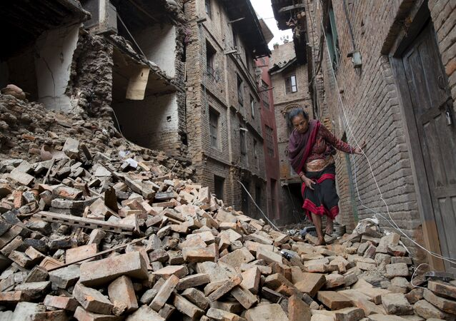 A woman walks across the rubble of a collapsed building following an earthquake in Bhaktapur near Kathmandu, Nepal in this Red Cross handout picture taken on April 28, 2015.