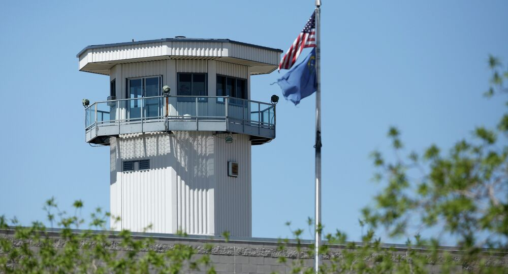 Flags fly near a guard tower at High Desert State Prison Wednesday, April 15, 2015, in Indian Springs, Nev