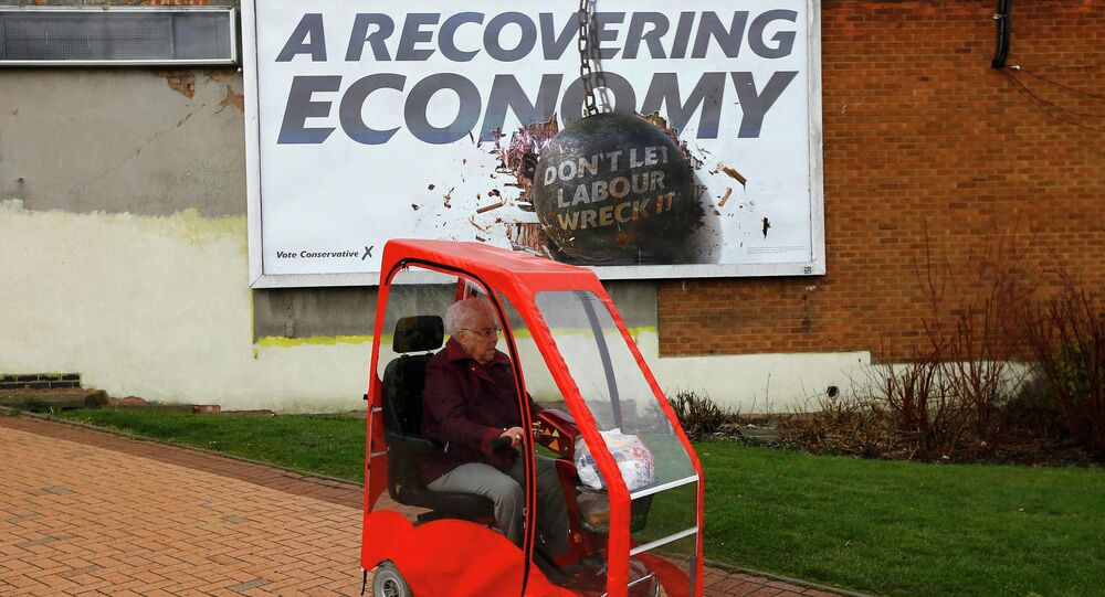 A woman drives a mobility scooter past a Conservative Party billboard in Bedworth, central England, April 1, 2015