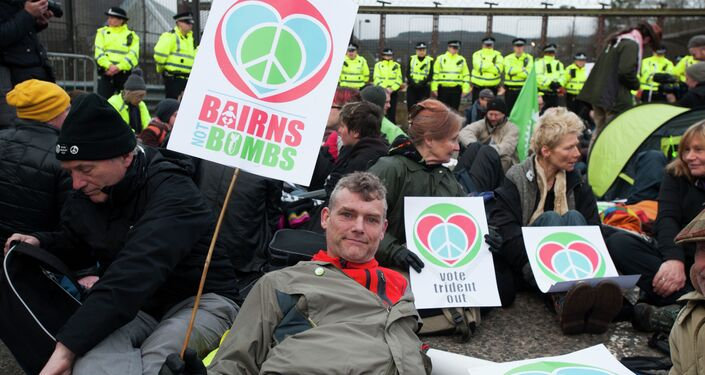 Protesters calling for an end to the Trident nuclear programme holds placards at a blockade in the road in front of HM Naval Base Clyde in Faslane, Scotland, northeast of Glasgow, on April 13, 2015 the UK base for Trident