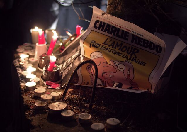 A copy of the Charlie Hebdo issue printed after the massacre at their Paris offices is placed at an impromptu memorial in Brussels during a solidarity gathering. The text reads Love is stronger than hate.