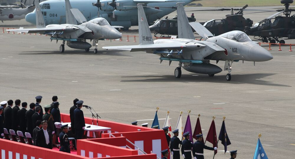 Japanese Prime Minister Shinzo Abe reviews Japan Self-Defense Forces' F-15J fighter jets at Hyakuri Airbase.