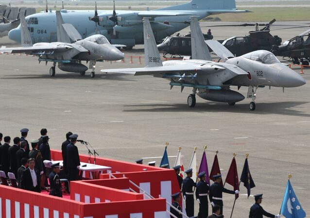 Japanese Prime Minister Shinzo Abe reviews Japan Self-Defense Forces' F-15J fighter jets at Hyakuri Air Base.