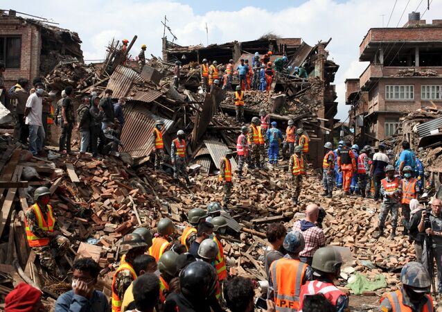 People watch as rescuers search for bodies at the site of a building which collapsed during an earthquake in Bhaktapur near of Kathmandu, Nepal in this Red Cross handout picture taken on April 29, 2015