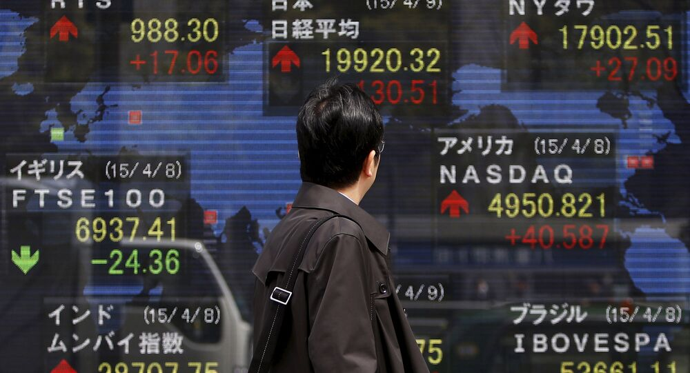 A pedestrian looks at an electronic board showing the stock market indices of various countries outside a brokerage in Tokyo April 9, 2015