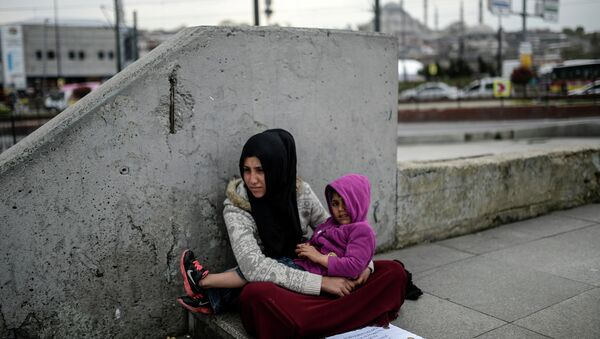 Syrian refugee woman begs as she sits with a child at Eminonu in Istanbul on April 14, 2015 - Sputnik International