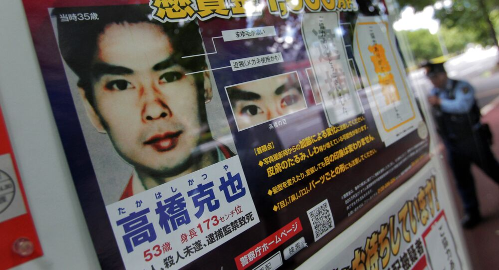A police officer walks near a wanted poster of former Aum Shinrikyo cult member Katsuya Takahashi displayed at the metropolitan police department in Tokyo