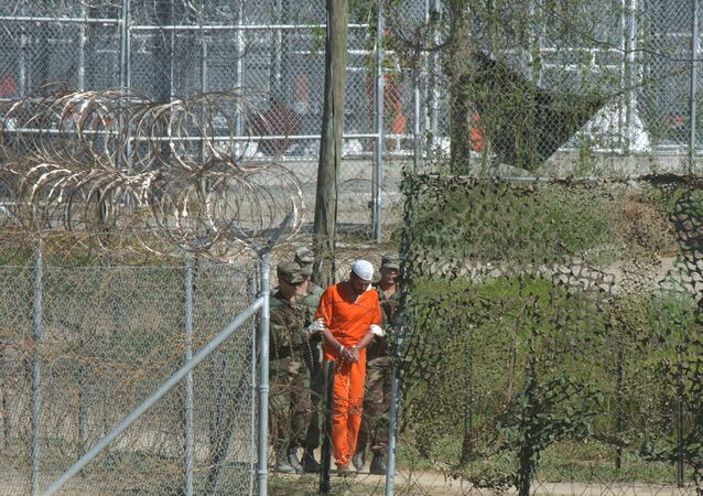 A detainee is escorted to interrogation by US military guards at Camp X-Ray at Guantanamo Bay.