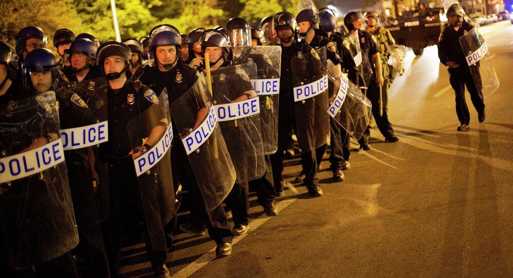 Police in riot gear line up near the scene of Monday's riots ahead of a 10 p.m. curfew Wednesday, April 29, 2015, in Baltimore. The curfew was imposed after unrest in Baltimore over the death of Freddie Gray while in police custody.