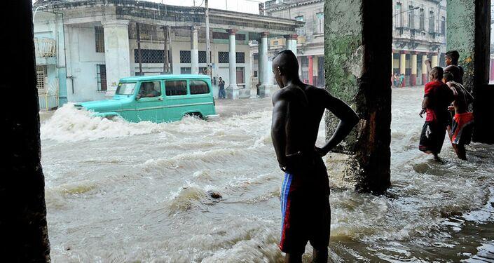 A car wades through a flooded street.