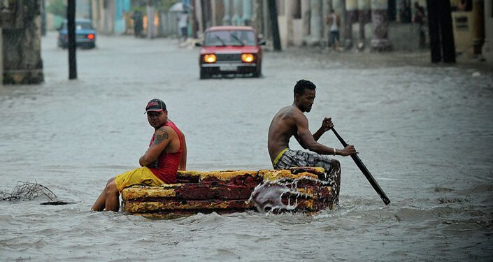 Two men on a makeshift raft sail through a flooded street.