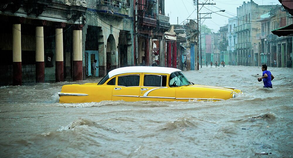 People and vehicles wade through a flooded street during an intense rainstorm in Havana, on April 29, 2015