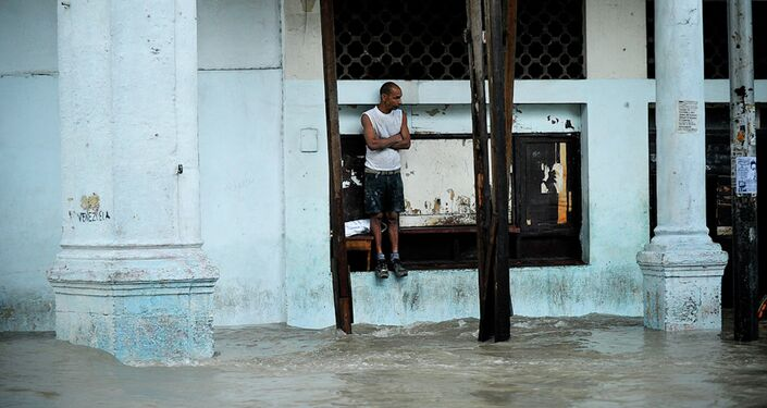 A pedestrian stands on the edge of a window at a flooded street.