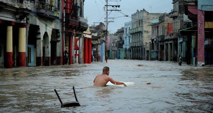 A man wades through a flooded street.