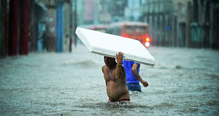 People wade through a flooded street.