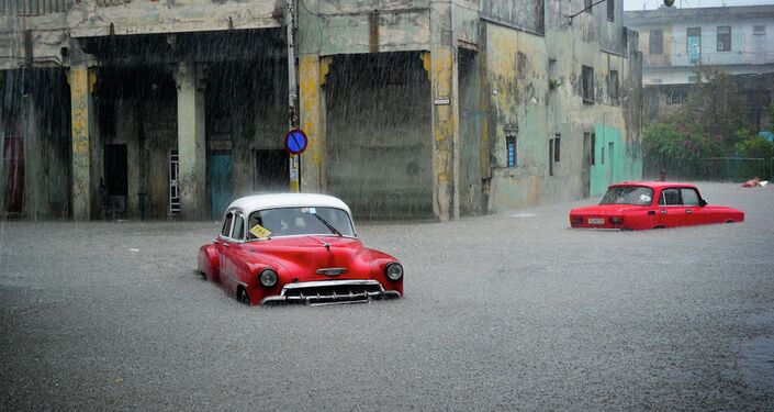 Stranded cars remain in a flooded street during an intense rainstorm in Havana.