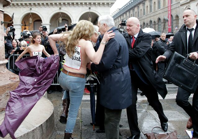 Femen activists with Le Pen Top Fascist painted on their bodies appear as France's far-right National Front president Marine Le Pen places a wreath at Joan of Arc statue during its annual May Day march, in Paris, France, Friday, May 1, 2015