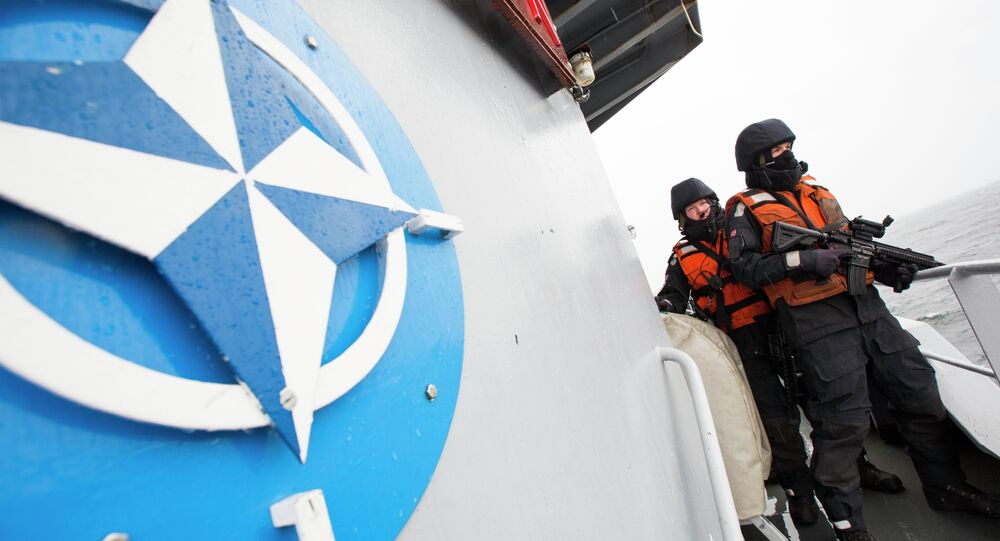 Two Norwegian sailors onboard the Norwegian support vessel Valkyrien pose for photographers next to the NATO logo