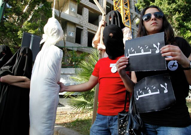 In this 2010 file photo, activists from a civil organization reenact an execution scene in front of the Saudi Arabia Embassy in Beirut, Lebanon, as they protest the beheading of a Lebanese man accused of witchcraft in Saudi Arabia.